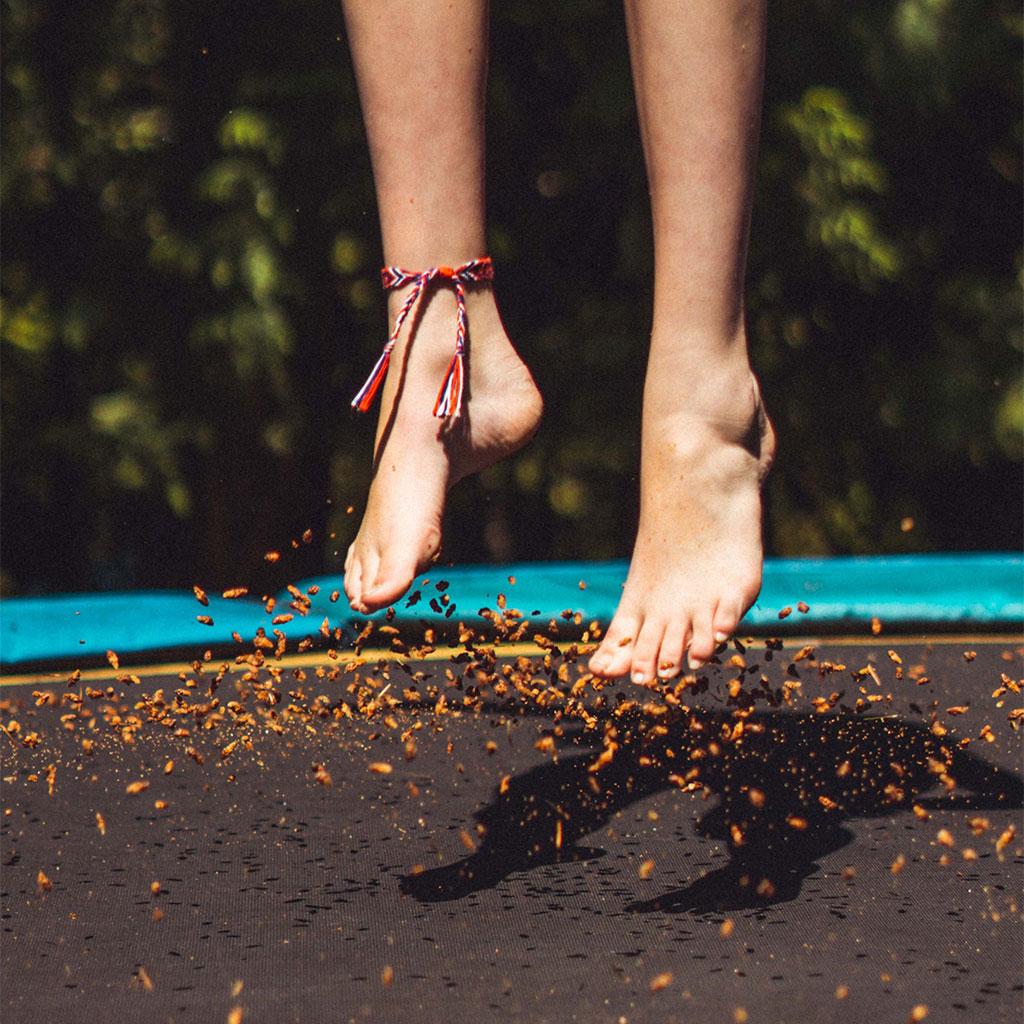 Photo d'une femme qui saute sur un trampoline pieds nus